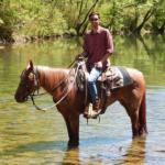 young man on horse in water