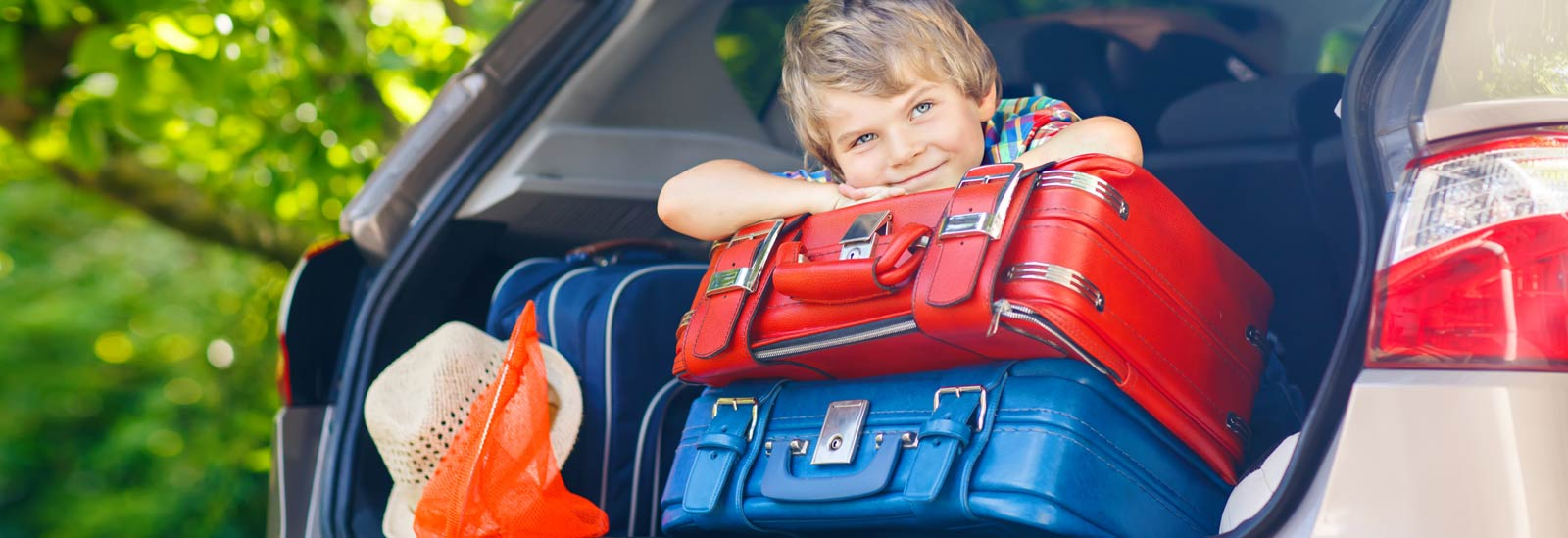 Boy in car with suitcases